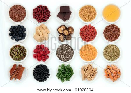 Healthy super food selection in porcelain bowls over white background.