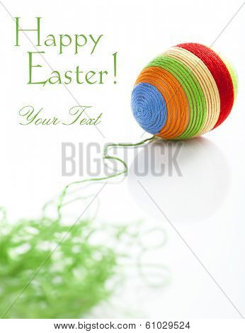 Easter egg covered with various colors wool. Bunch of green wool on first plan. Space for text