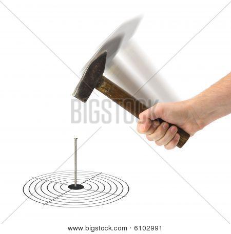 Hand mit Hammer und Nagel im Ziel