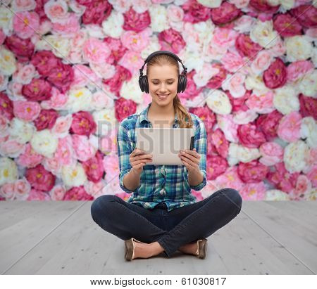 technology, internet and people concept - smiling young woman in casual clothes sitiing on floor with tablet pc computer and headphones