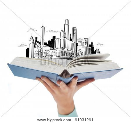 education and book concept - close up of woman hand holding open blue book with city sketch