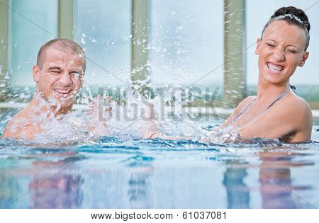 Young attractive female and handsome male splashing in a swimming pool
