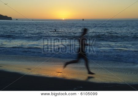 Man Running On The Beach And Sunset