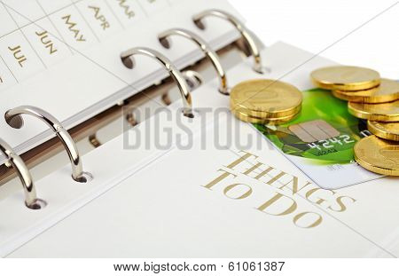 Credit Card, Golden Coins  On The Page Of An Organizer. Selective Focus
