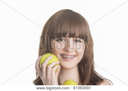 Happy Young Caucasian Girl With Brackets On Teeth Holding Two Green Apples