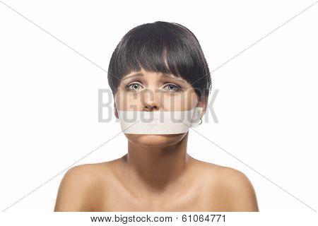 Family Violence Concept: Portrait Of Brunette Woman With Her Mouth Sealed With Tape