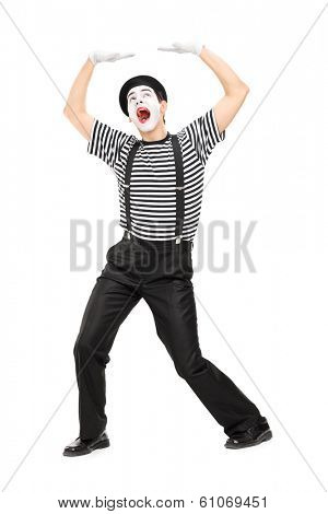 Mime artist simulate carrying something over his head isolated on white background
