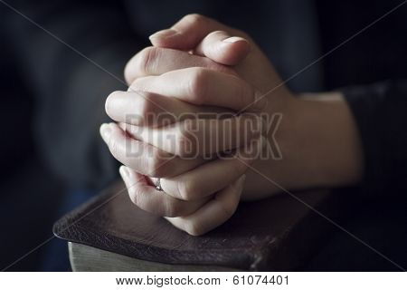 Folding Hands over a Bible