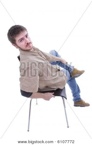 Full Body Of A Young Handsome Casual Man Relaxing In A Chair.