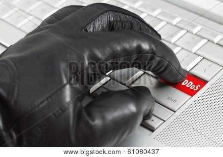 Online Spy Ware Concept With Hand Wearing Black Leather Glove Pressing Enter Key On Metallic Laptop