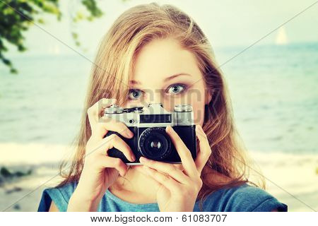 Pretty girl making photo using classic slr camera.