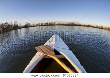 bow of white decked canoe with wooden paddle on a calm lake in Colorado - a fish eye lens perspective