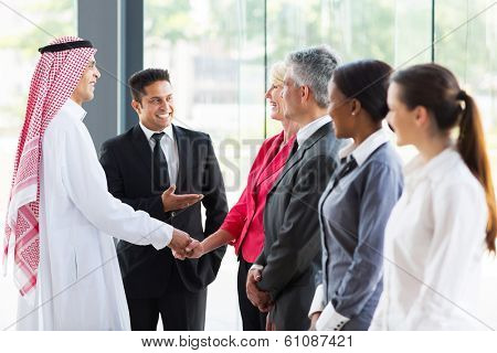young translator introducing Arabian businessman to business partners