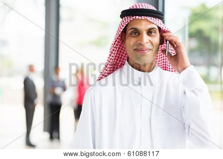 smiling arabian businessman talking on cell phone