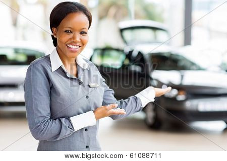 friendly african car saleswoman presenting new vehicles