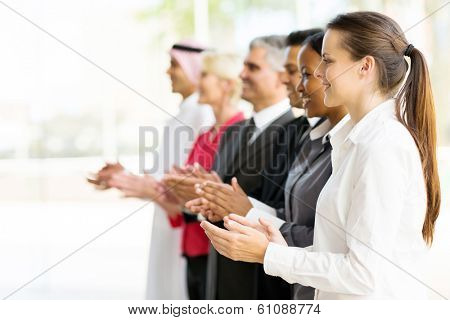 group of multicultural business partners applauding