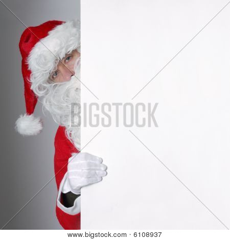 Santa Claus Looking From Behind An Ad Space
