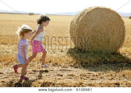 Girls Playing With The Round Wheat Dried Bales