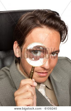 Young Businessman With A Magnifying Glass