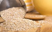 stock photo of oats  - Healthy steelcut whole oats spilling out of a measuring cup - JPG