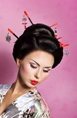 foto of geisha  - Portrait of a Japanese geisha woman on the pink background - JPG