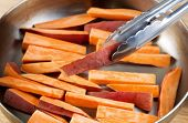 pic of tong  - Horizontal photo of freshly cut Yams in stainless steel frying pan with focus on single piece being place into pan with tong
