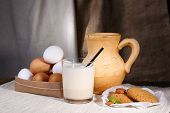Eggnog with milk and eggs on table and fabric background