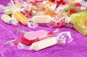 Tasty candies on purple background
