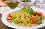 stock photo of pesto sauce  - Delicious pasta with pesto on plate on table close - JPG