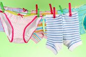 stock photo of wet pants  - Baby clothes hanging on clothesline - JPG