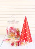 Tasty candies in jar with party hat on table on wooden background