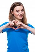 stock photo of sweethearts  - Happy young woman making a romantic heart gesture symbolising her love or affection for a sweetheart or loved one Valentines concept isolated on white - JPG