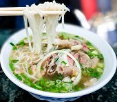 stock photo of brisket  - Bowl of Vietnamese pho noodle soup with rare beef tendon tripe and brisket served with onions scallions and cilantro - JPG
