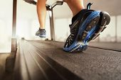 stock photo of soles  - Man running in a gym on a treadmill concept for exercising - JPG