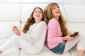 Children friends kid girls having fun playing back to back with tablet pc on white sofa