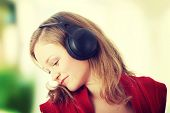 Listening to the Music, young caucasian beautiful blond woman with headphones