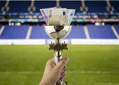 stock photo of money prize  - hand lifting a trophy with euros in more money concept with more titles fund a stadium - JPG