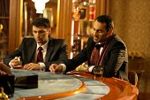 picture of roulette table  - Two young men in suits behind gambling table in a casino - JPG