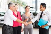 stock photo of showrooms  - happy middle aged man handshake with car salesman after purchasing a car - JPG