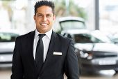 foto of showrooms  - happy young indian car salesman in showroom - JPG