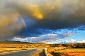 Low swirling cloud and flat plain covered in orange sunset. Cloud crosses the rainbow. In the stepp