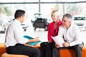stock photo of showrooms  - vehicle salesman explaining contract to senior couple before buying a car - JPG