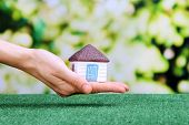 Little paper house in hand close-up, on green grass, on bright background