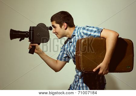 Young Filmmaker With Old Movie Camera And A Suitcase In His Hand.