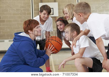 Coach Giving Team Talk To Elementary School Basketball Team