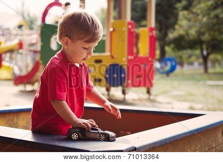 Young Boy Playing With Toy Car In Sandbox