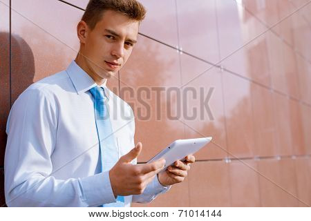 Businessman With Tablet Computer Looking At Camera