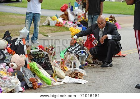 FERGUSON, MO/USA - AUGUST 30, 2014: A man places shirt at makeshift memorial where black teenager Michael Brown was shot to death by police in Ferguson, Missouri.