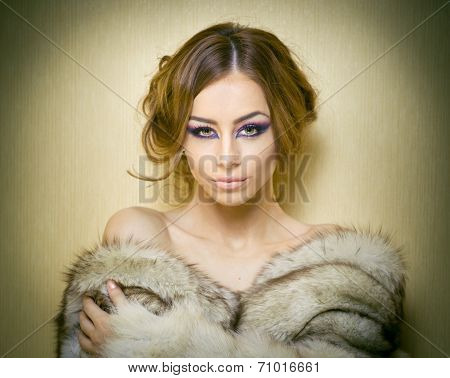 Attractive sexy young woman wearing a fur coat posing provocatively indoor. Portrait of sensual girl