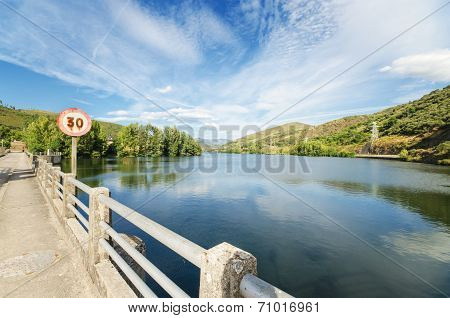 Scenic view of a road and lake in a mountain scenary.